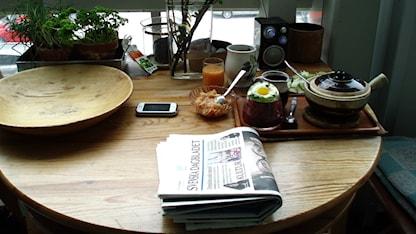 En bricka med uppdukad frukost på ett runt bord i ett kök.
