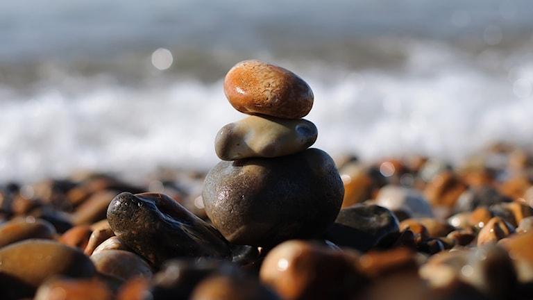 Tre stenar staplade på varandra i vattenbrynet på en strand.
