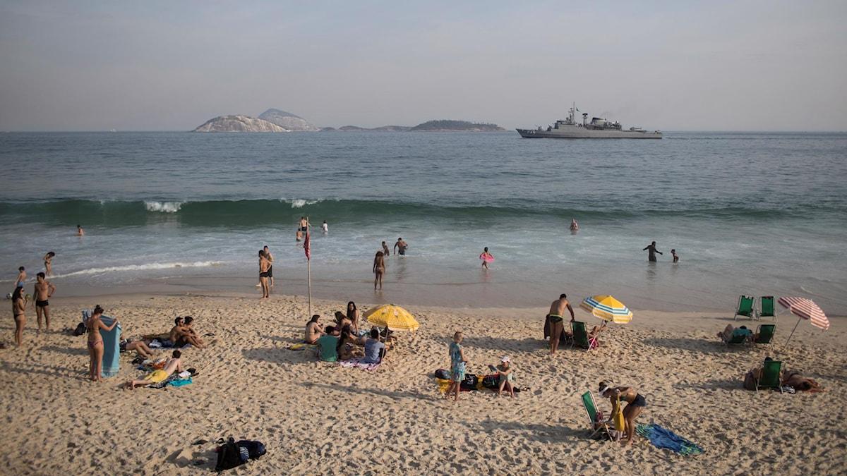 Människor solar och badar på Ipanemastranden.