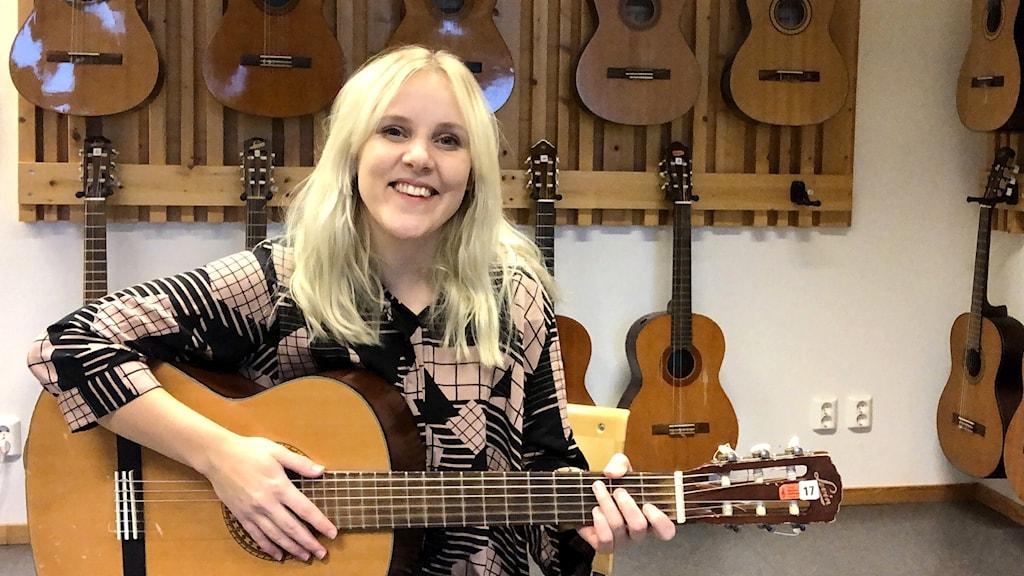 Musikläraren Jonna Ydenius sitter och håller i en gitarr i en musiksal på en högstadieskola. I bakgrunden hänger fler klassiska gitarrer på väggarna.