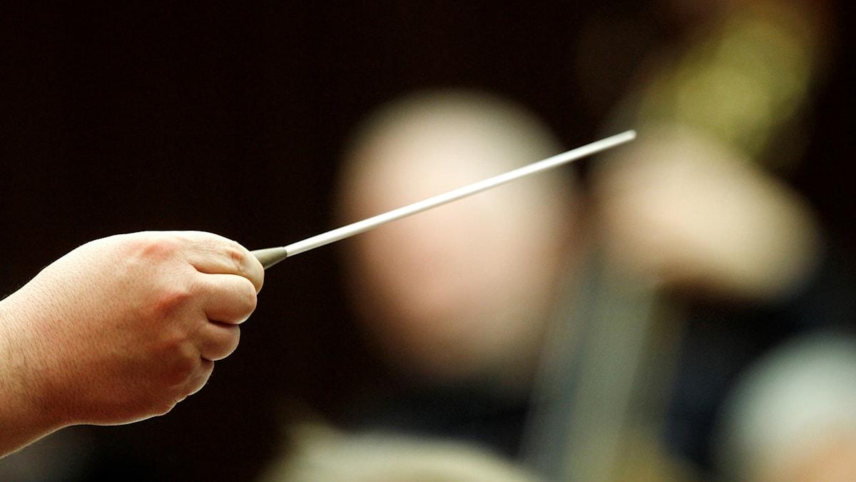 Närbild på hand som håller i en dirigentpinne framför en orkester.