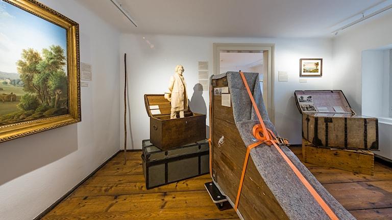 Prylar på Beethovens museum i Wien. En tavla på väggen, en koffert ur vilken en Beethovenstaty tittar upp, och ett flyttpackat klaverinstrument.