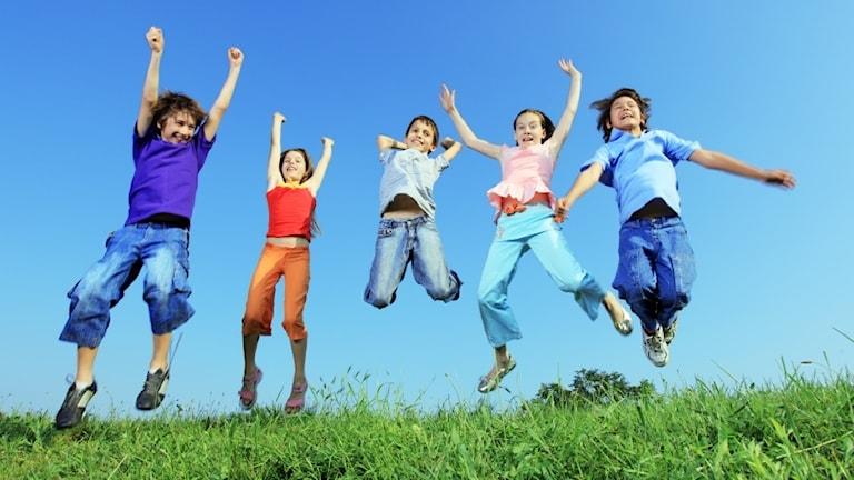 Glada barn som hoppar i gräset och sträcker armarna i luften.