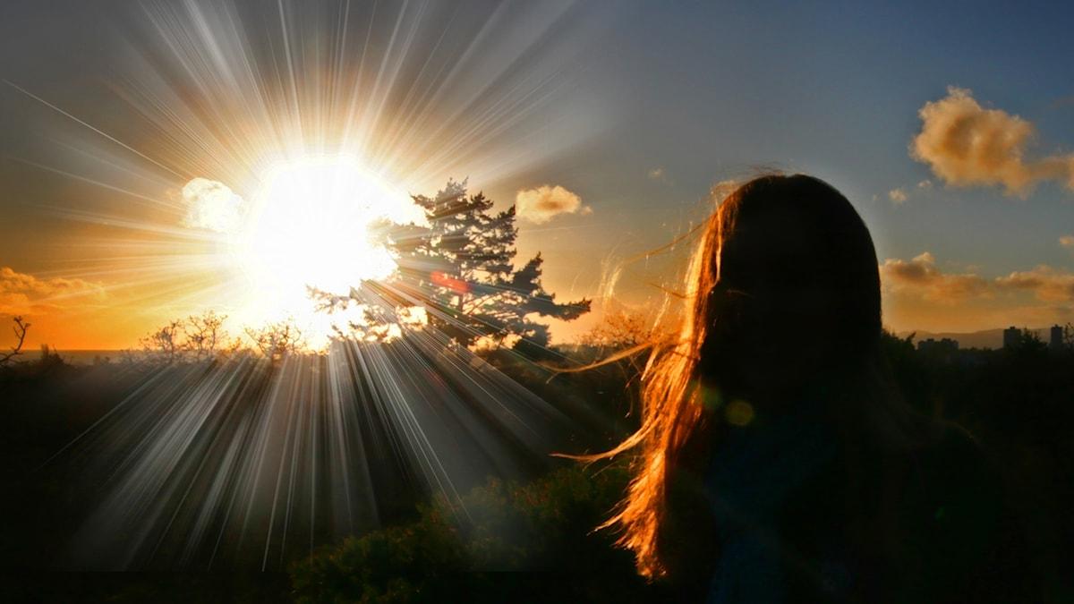 Siluetten av en flicka bredvid solen som strålar.