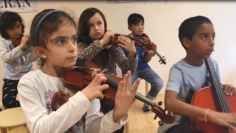 Barn som spelar fiol och cello.