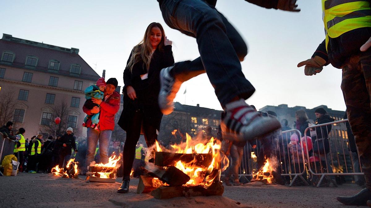 Personer som hoppar över små eldar under eldfesten.