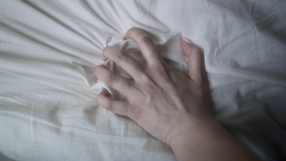 En hand griper tag i ett lakan.