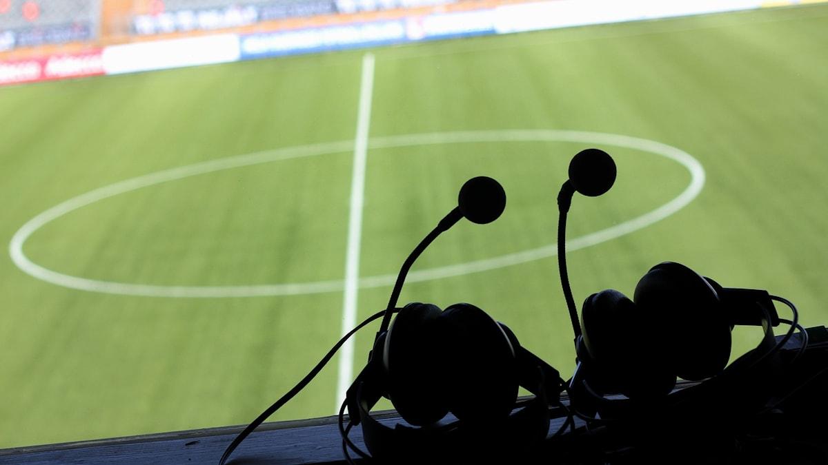 Två sportkommentator-headset som ligger i kommentatorsbåset på en fotbollsarena.