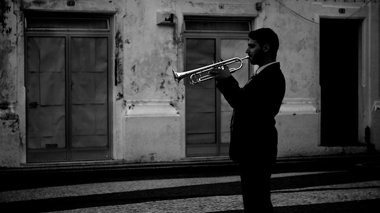 Siluetten av en man som spelar trumpet på en bakgata.