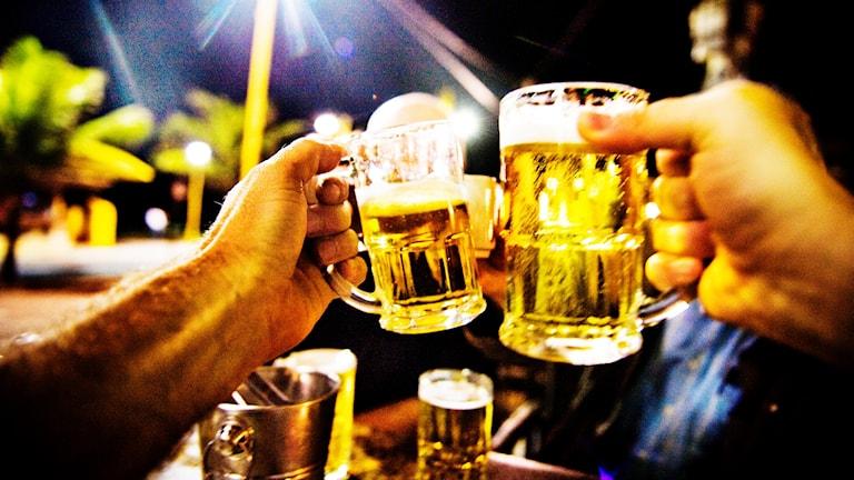 Ölsejdlar som hålls av manliga armar slås samman i en skål.