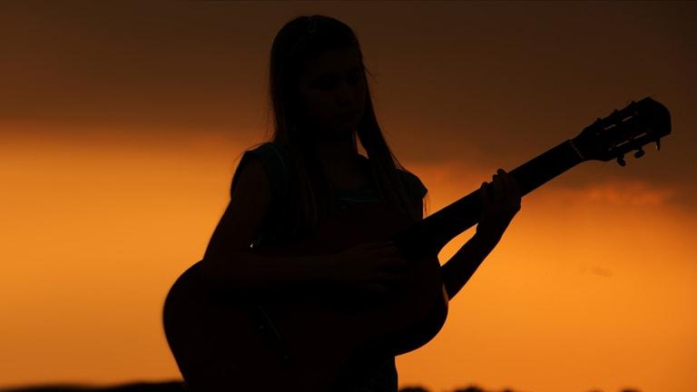 Siluetten av en kvinna som spelar gitarr.