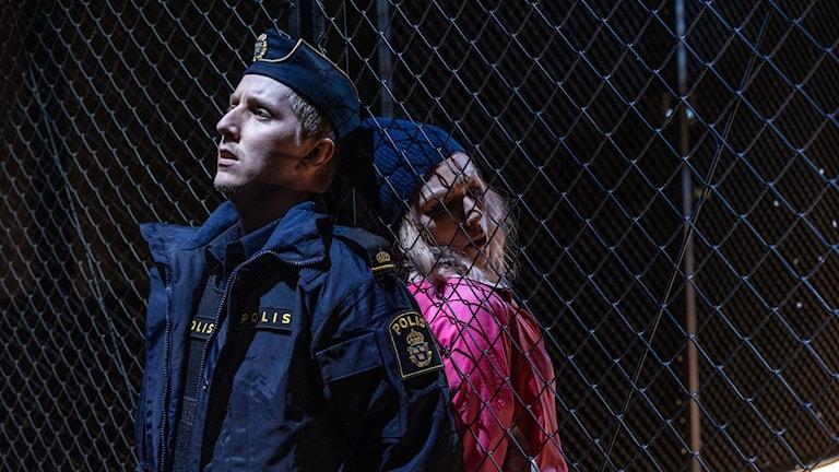 William Davis Lind i polisuniform i rollen som Don José och Solgerd Isalv som Carmen i Vermland Operas uppsättning. De står med ryggarna mot varandra på varsin sidan om ett stängsel.