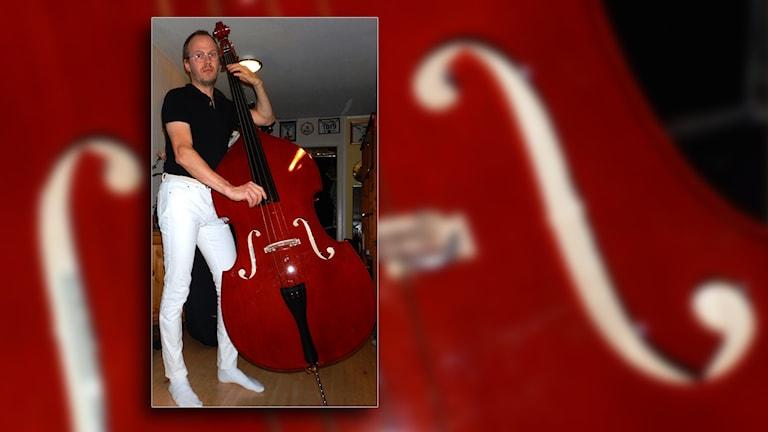 Jonas Magnusson står och spelar på sin kontrabas i sitt hem.