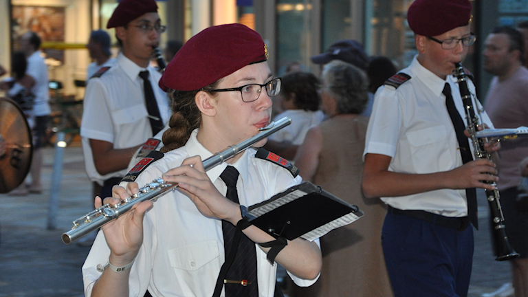 Melissa Freij marscherar med sin blåsorkester och spelar på sin tvärflöjt.