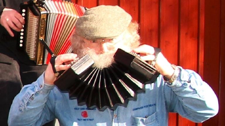 Rickard Kumlien håller upp sin concertina som en glad mun framför sin haka.