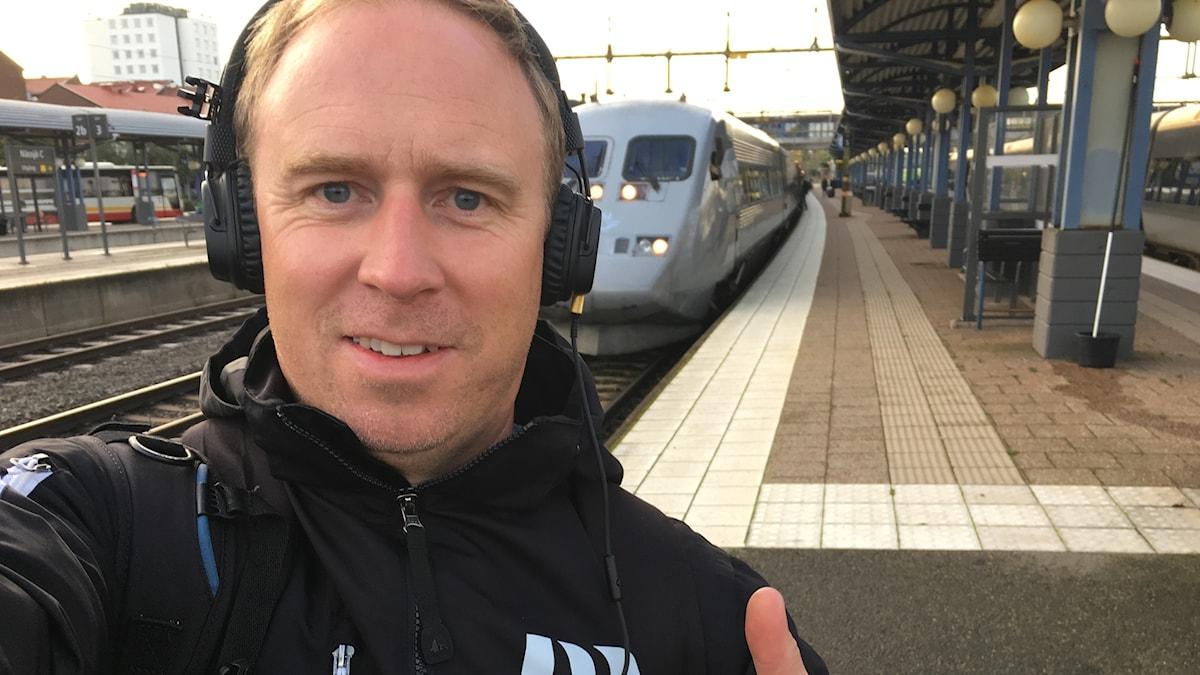 Martin Ekeholm med hörlurar på huvudet sänder direkt från stationen i Nässjö. I bakrunden ett snabbtåg på spår 5.
