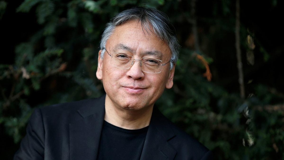 Nobelpristagaren i litteratur Kazuo Ishiguro framför ett buskage.