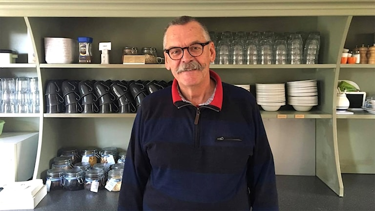 Bjerne von Schulman framför en bänk i frukostmatsalen på sitt hotell. I bakgrunden rader av glas och koppar i en hylla.
