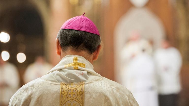 En katolsk ärkebiskop med kalott på hjässan sedd bakifrån.