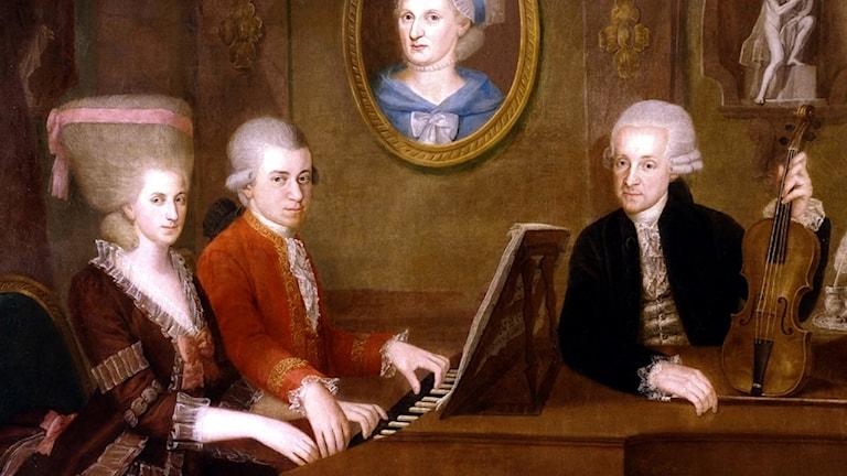 Familjeporträtt av familjen Mozart av Johann Nepomuk della Croce. Storasyster Maria Anna Nannerl och hennes bror Wolfgang Amadeus vid ett klaverinstrument, mamma Anna Maria på en tavla på väggen och pappa Leopold med en fiol i handen.