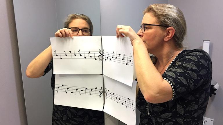 Pernilla Eskilsdotter håller upp två blad med noter så att de blir spegelvända i en spegel.