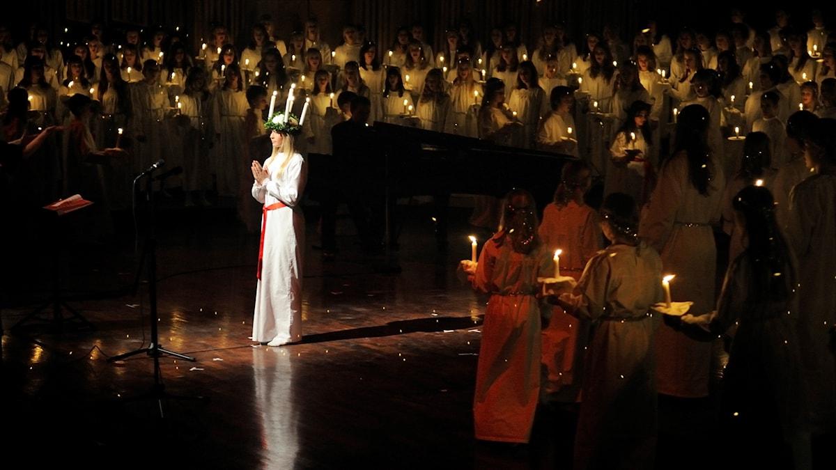 Lucia och hennes tärnor med tända ljus.