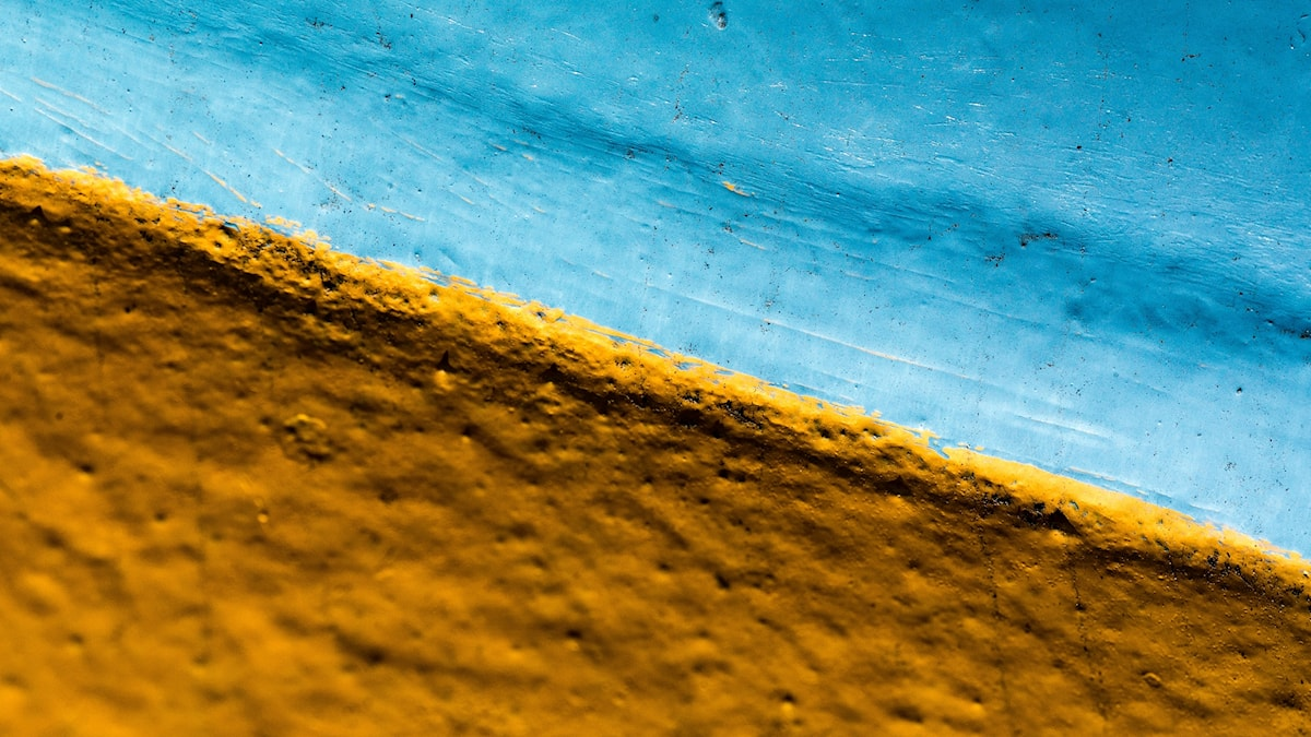 Blå och gul målarfärg på betong formar Ukrainas flagga.