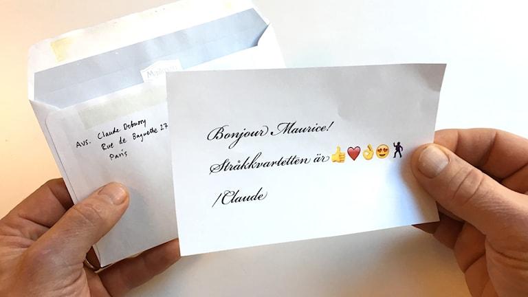 Två händer håller i ett brev som precis plockats upp ur ett kuvert.