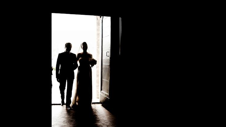 Siluett av bröllopspar på väg in genom en dörröppning.