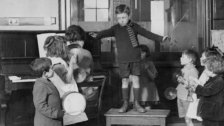 Barn med instrument tittar upp på jämnårig kamrat som står på en pall och är dirigent.