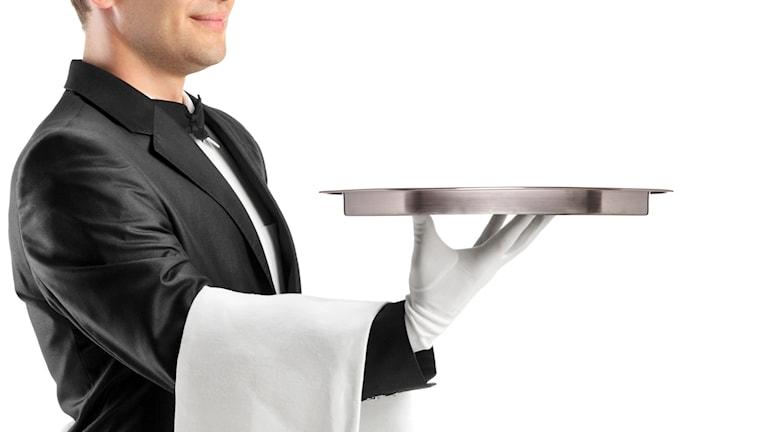 En manlig butler balanserar en silverbricka med sin handskbeklädda fingrar.
