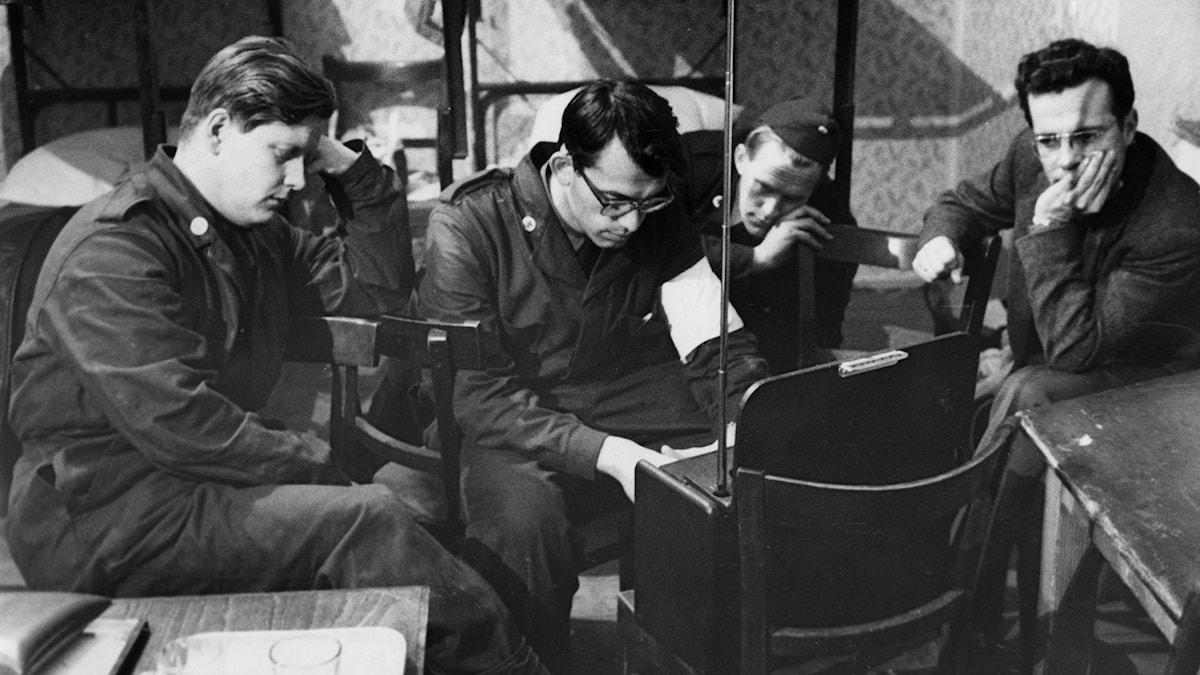 Fyra militärer sitter runt en radio på ett logement.