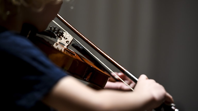 Barn spelar fiol, närbild
