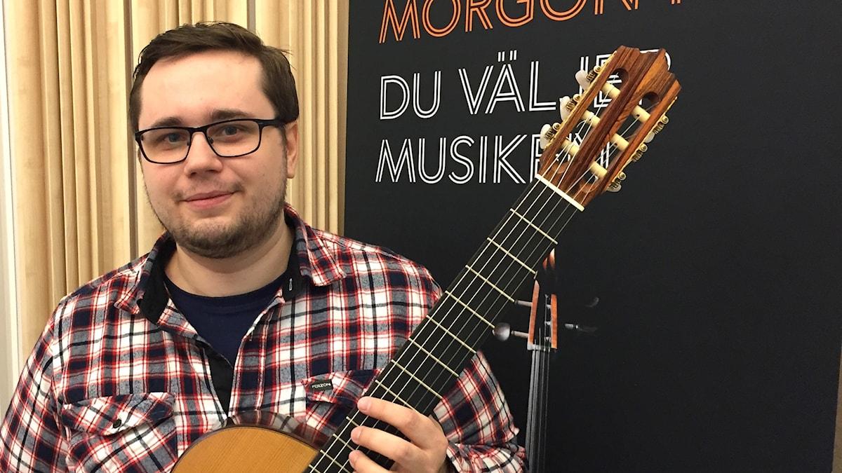 Gitarrläraren Emil Nordén med sitt instrument i radiostudion i Växjö.