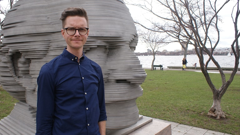 Karl-Oskar Freij står framför en staty bestående av ett stort huvud.