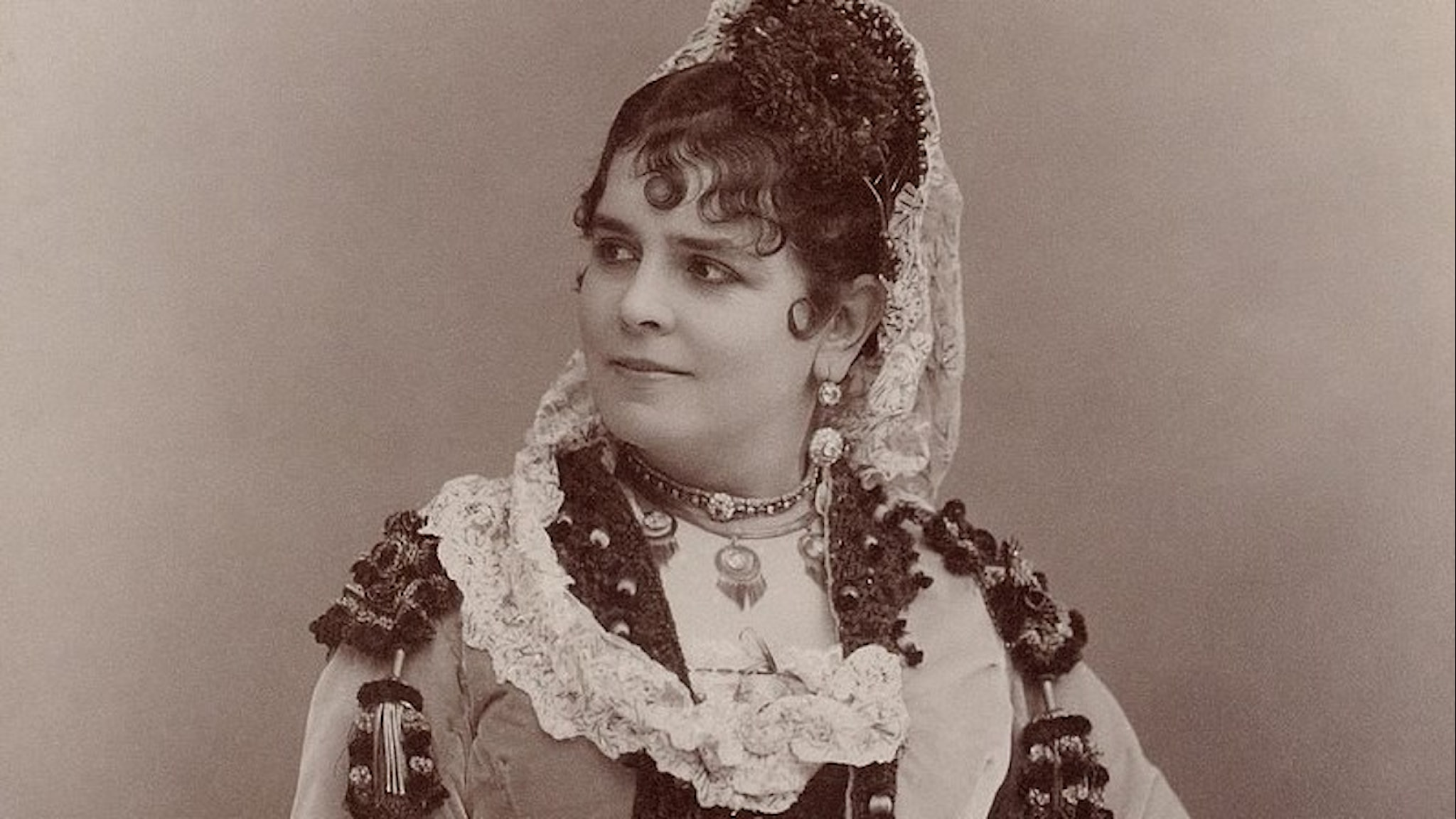 Tjusig kvinna med uppsatt hår, spetsar runt halsen och mycket smyckad