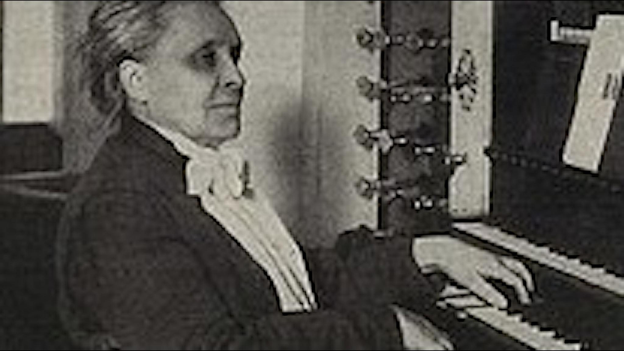 En kvinna som sitter vid spelbordet till en stor kyrkorgel