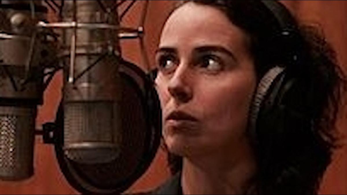 Clarice Assad i inspelningstagen framför en gammal fin rörmikrofon!