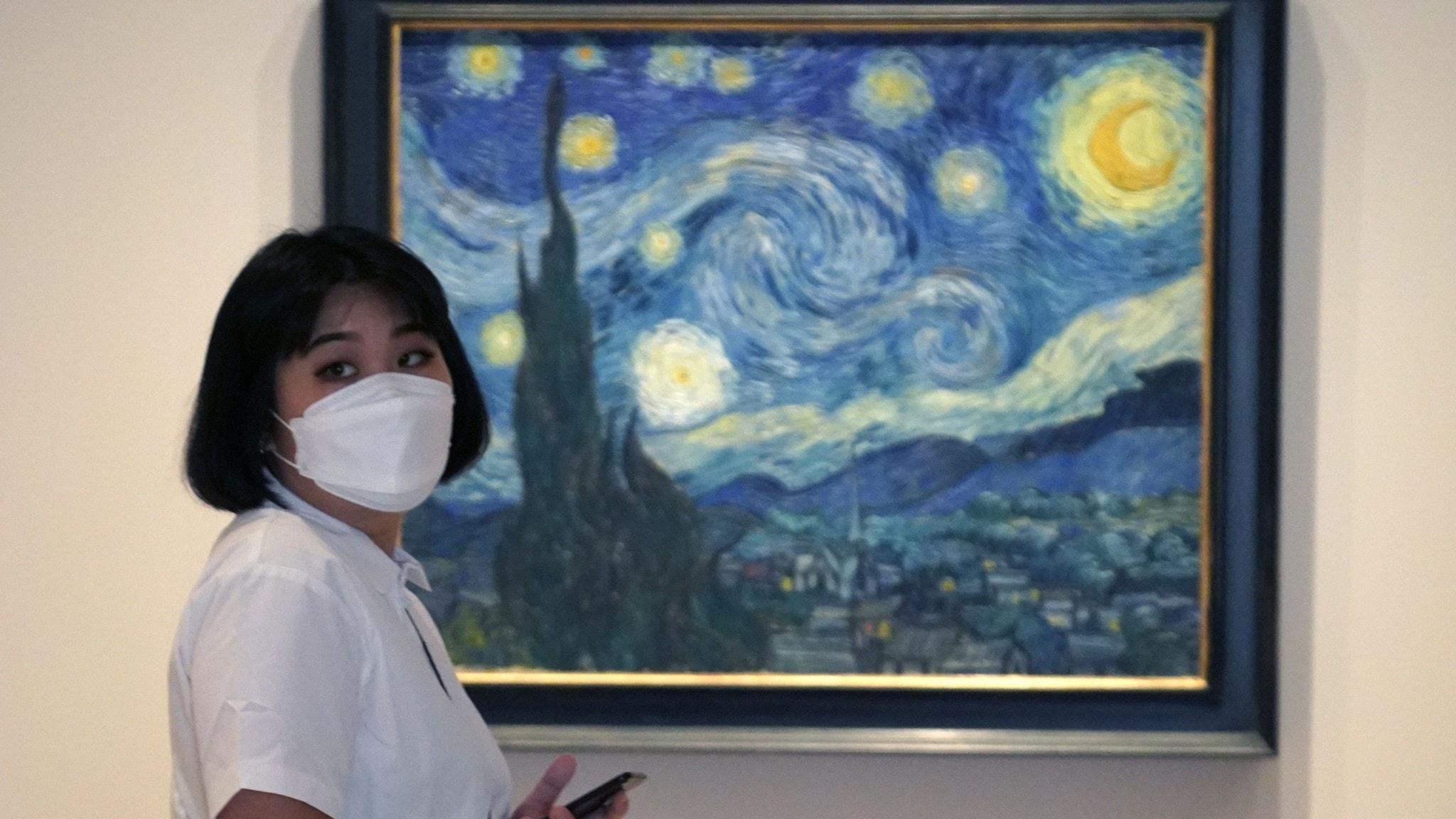 Kvinna i munskydd framför Vincent van Goghs målning Stjärnenatt