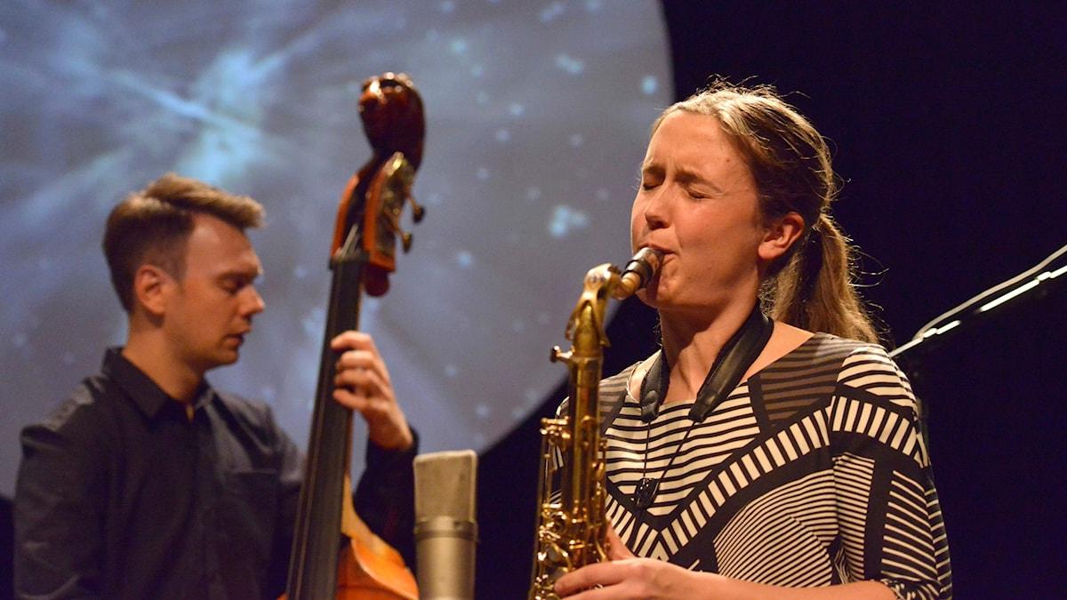 Tenorsaxofonisten och kompositören Hanna Paulsberg, i bakgrunden basisten Trygve Waldemar Fiske.