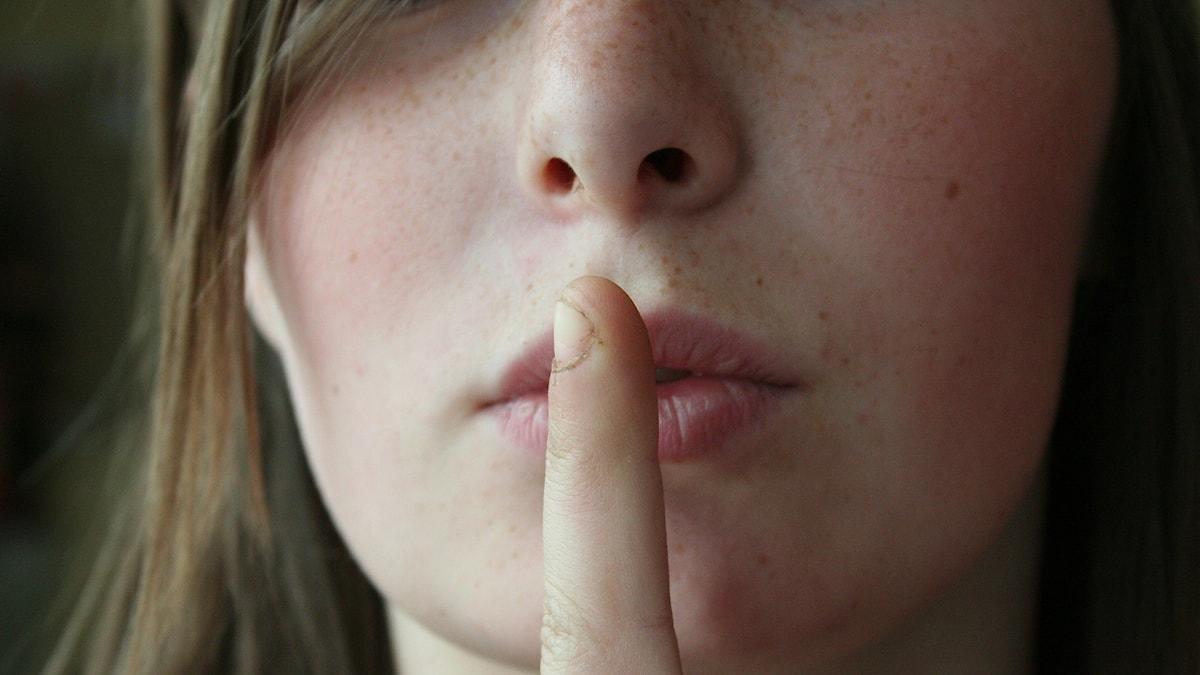Kvinna som står med sitt finger för munnen, som för att tysta någon.