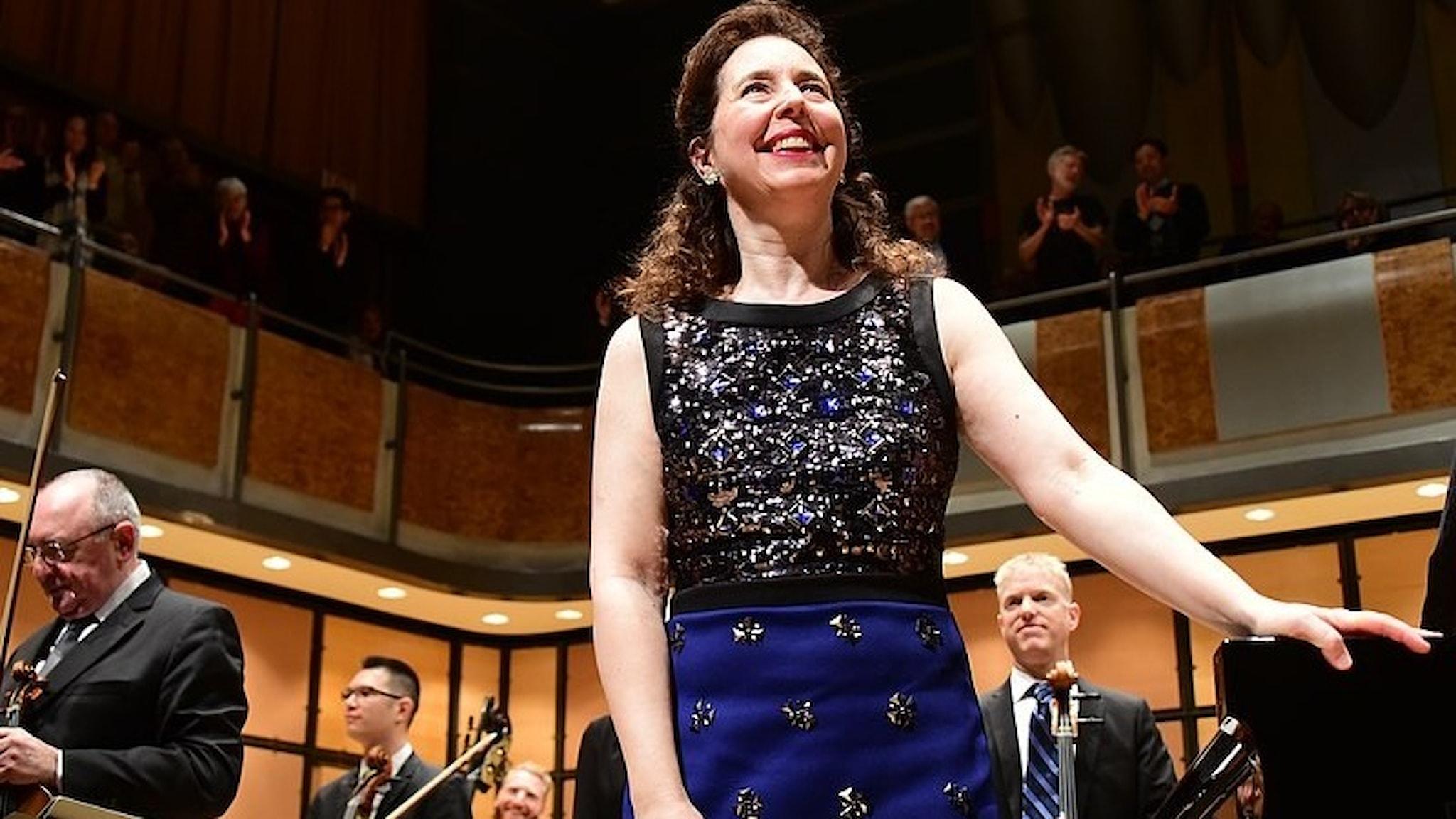 Pianisten Angela Hewit står vid flygel och tar emot applåder.