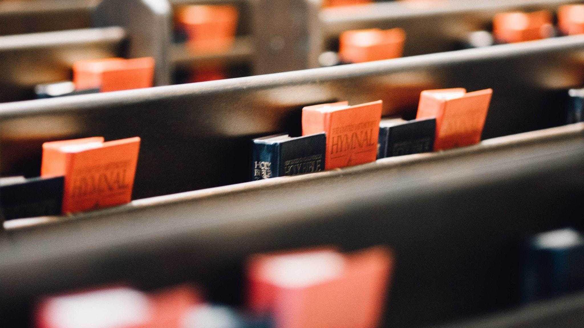 Kyrkobänkar med psalmhäften och bibeln, men inga människor.
