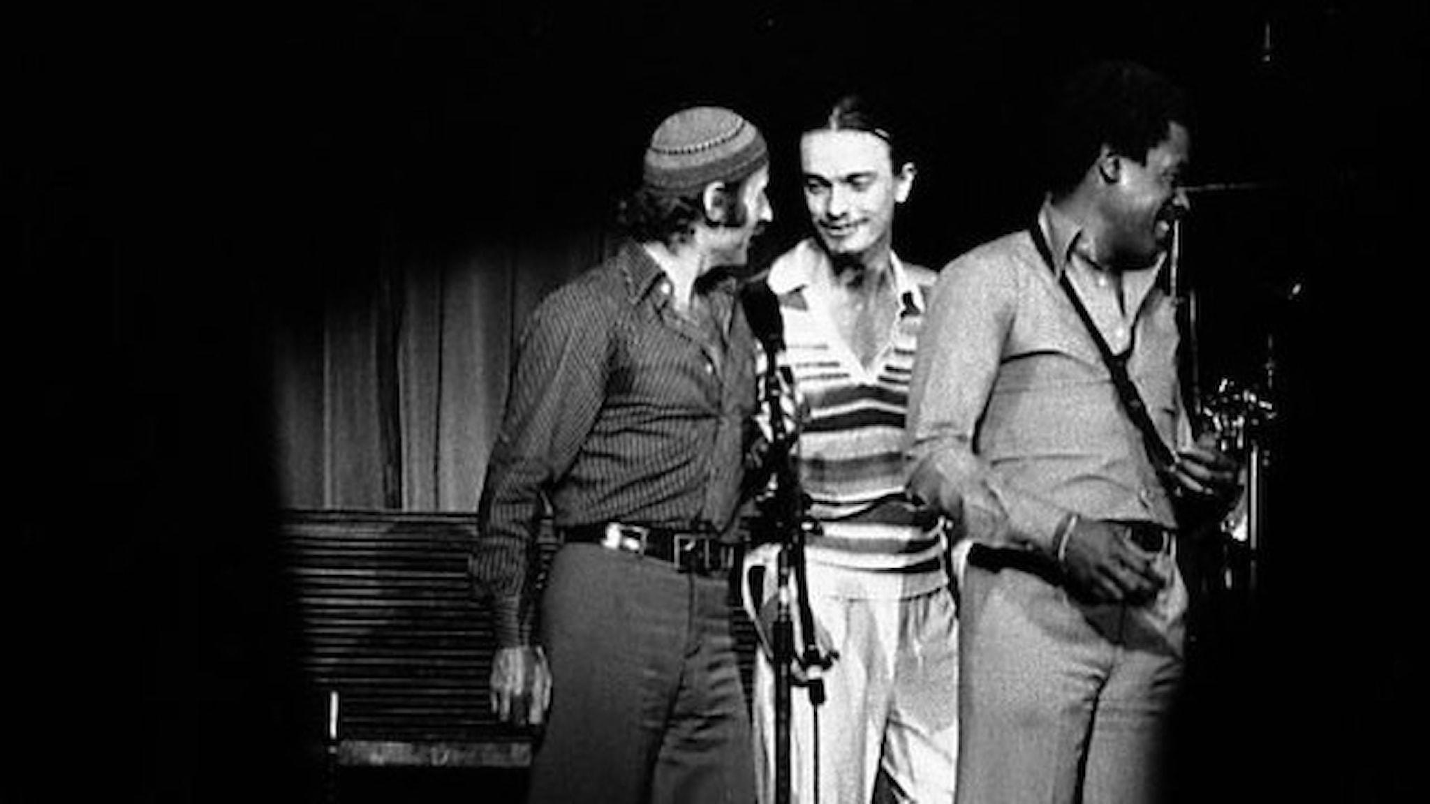 Svartvit bild på Weather Report i Toronto 1977. Joe Zawinul, Jaco Pastorius och Wayne Shorter står på en scen troligen efter konserten. Foto: Wikimedia commons.