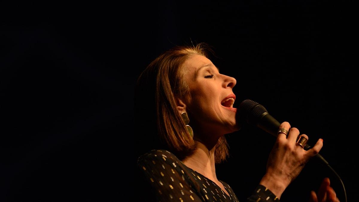 Kvinna som sjunger i en mikrofon