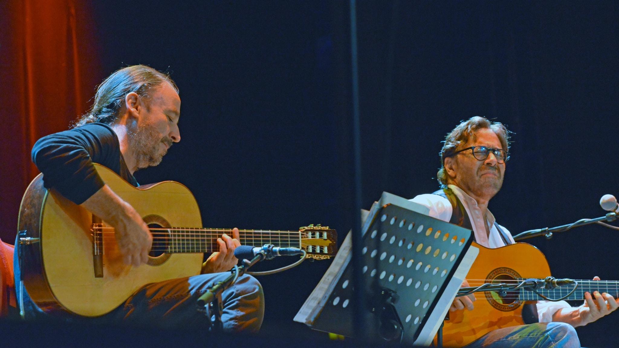 Två gitarrister på en konsertscen