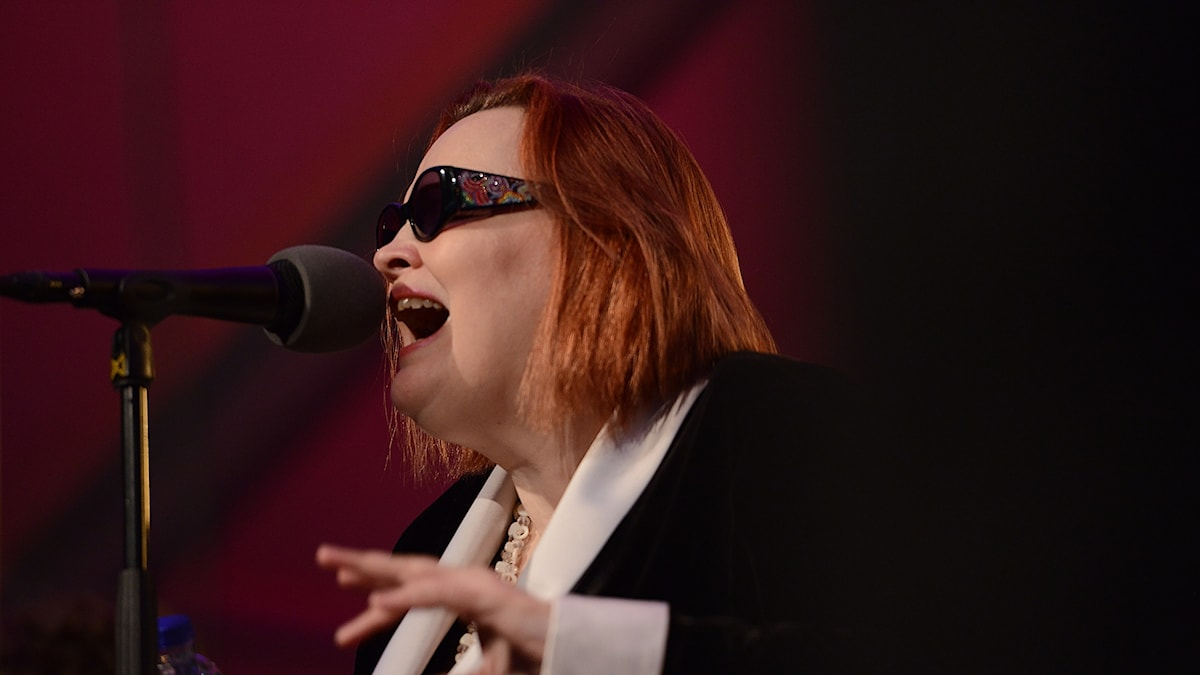 Kvinna med solglasögon, som sjunger i en mikrofon.
