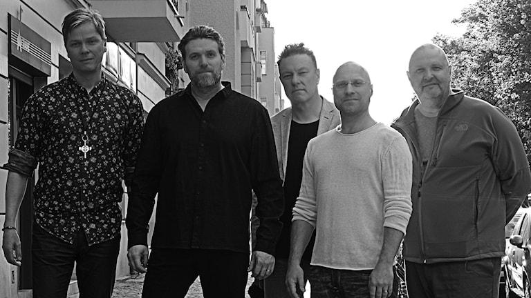 Svartvit bild av fem män på en trottoar.