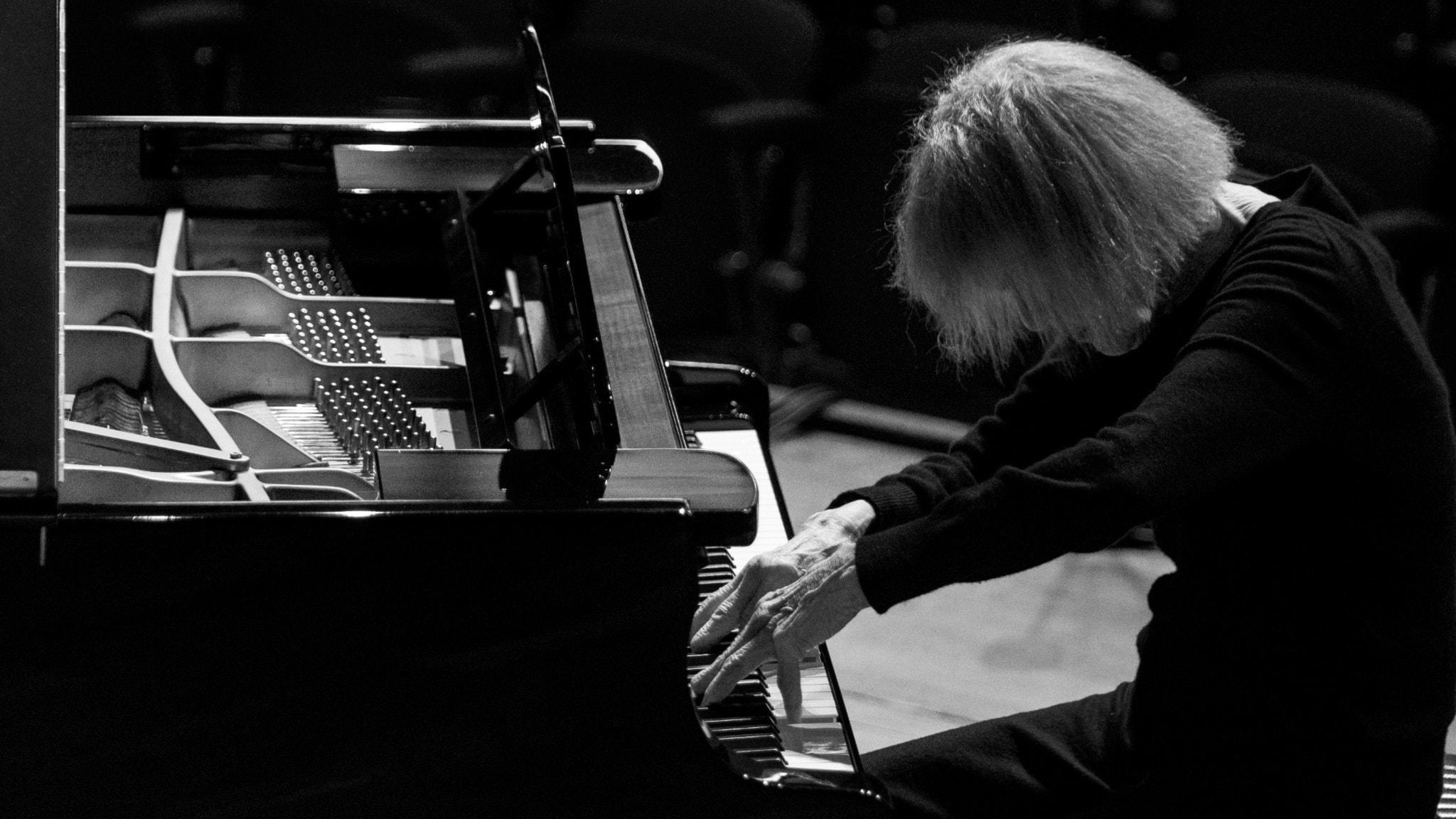 Svartvit bild på kompositören och pianisten Carla Bley när hon sitter med nedsänkt huvud och spelar på en flygel i en konsertsal utan publik. Foto: Caterina di Perri/ECM