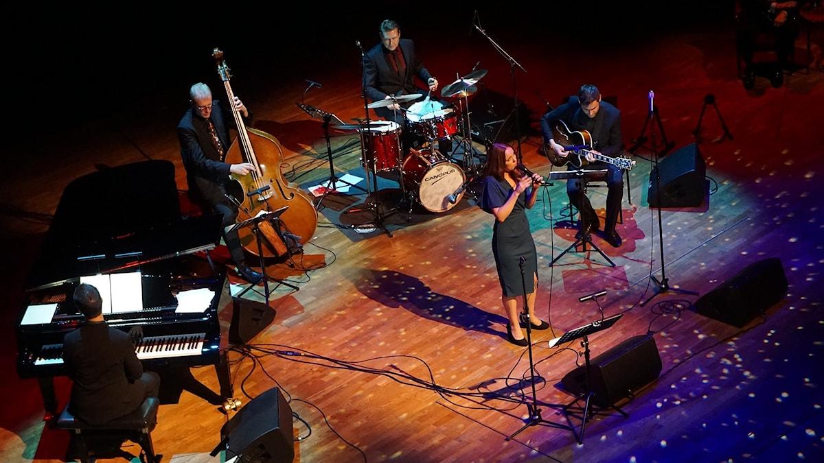 Fyra musiker och en sångerska på en scen.
